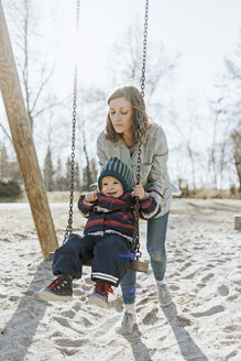 Mother with little daughter on swing on a playground - DWF00414