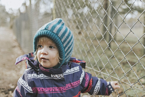Toddler girl in warm clothes at a fence in forest - DWF00423