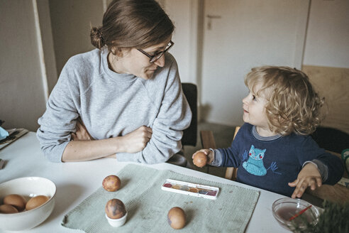 Mother and daughter sitting at table at home painting Easter eggs - DWF00432
