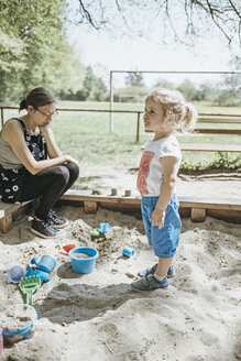 Mother playing with little daughter in sandbox on a playground - DWF00438