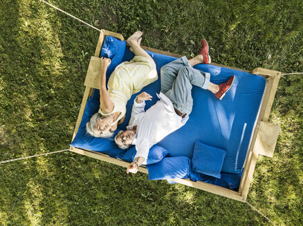 Elderly couple lying on swing bed, watching drone - PESF01556