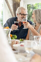 Senior couple celebrating with their family, clinking glasses - PESF01601