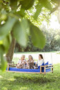 Women of a family relaxing in garden, sitting on a swing bed - PESF01607
