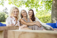 Women of a family having fun in the in garden, sitting on a swing bed - PESF01613