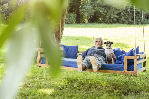 Senior man relaxing on a swing bed in his garden with his dog - PESF01616