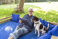 Senior man relaxing on a swing bed in his garden, using digital tablet - PESF01619