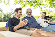 Men of a family sitting on a swing bed ing the garden, talking - PESF01622