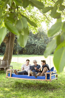 Men of a family sitting on a swing bed ing the garden, talking, using digital tablet - PESF01628