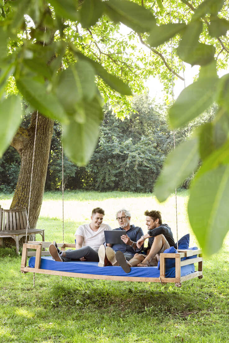 Men of a family sitting on a swing bed ing the garden, talking, using digital tablet - PESF01628 - Peter Scholl/Westend61
