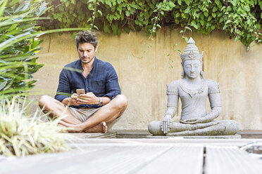 Man sitting cross-legged next to Buddha statue in a Zen garden, using smartphone - PESF01631