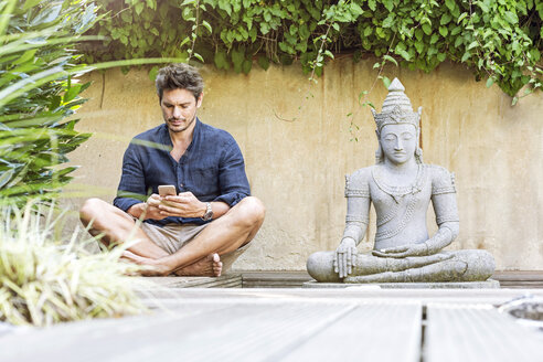 Man sitting cross-legged next to Buddha statue in a Zen garden, using smartphone - PESF01631