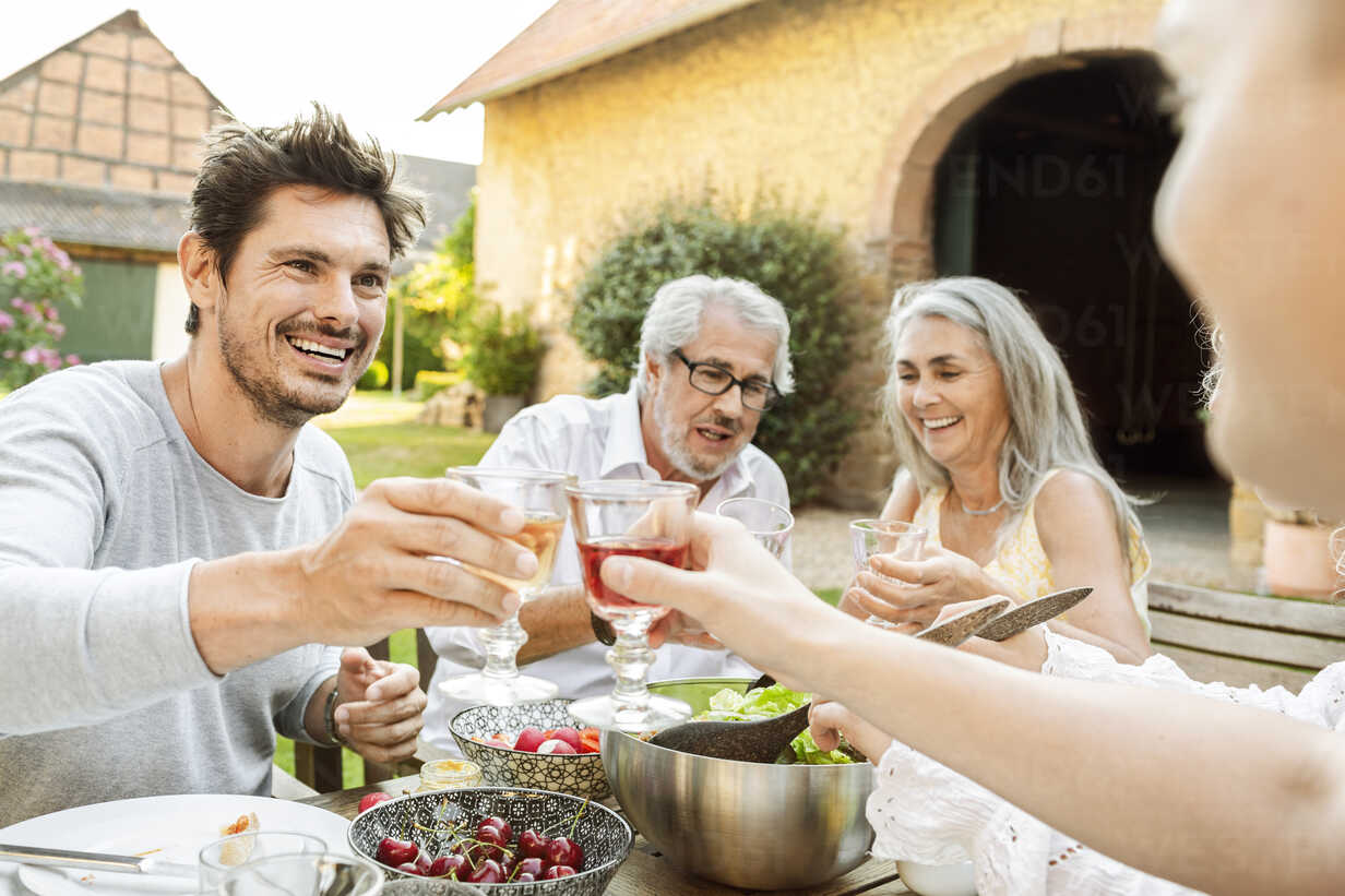 Happy family eating together in the garden, clinking glasses - PESF01640 - Peter Scholl/Westend61
