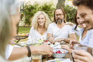 Happy family eating together in the garden - PESF01649