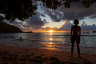 Seychelles, Mahe, Takamaka Beach, silhouette of man standing on the beach watching sunset - NDF00922