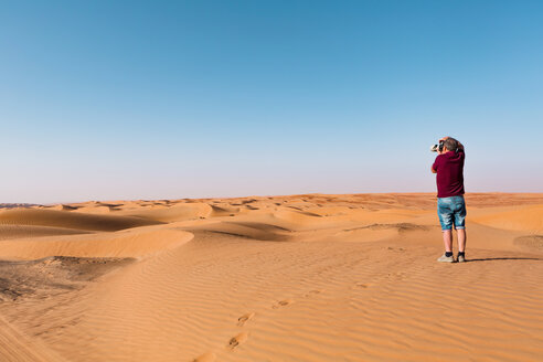 Senior man taking pictures of the desert, Wahiba Sands, Oman - WVF01302