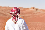 Bedouin in National dress standing in the desert, rear view, Wahiba Sands, Oman - WVF01344