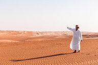 Bedouin in National dress standing in the desert, pointing at distance, Wahiba Sands, Oman - WVF01359
