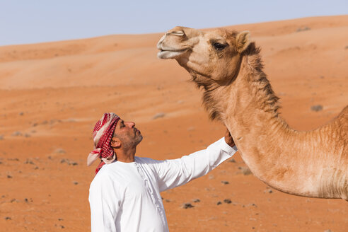 Bedouinn stroking his camel in the desert, Wahiba Sands, Oman - WVF01362