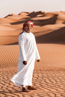 Bedouin in National dress standing in the desert, Wahiba Sands, Oman - WVF01380