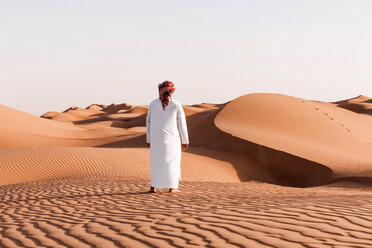 Bedouin in National dress standing in the desert, rear view, Wahiba Sands, Oman - WVF01383