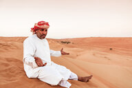 Bedouin in National dress sitting on sand dune in the desert, Wahiba Sands, Oman - WVF01410