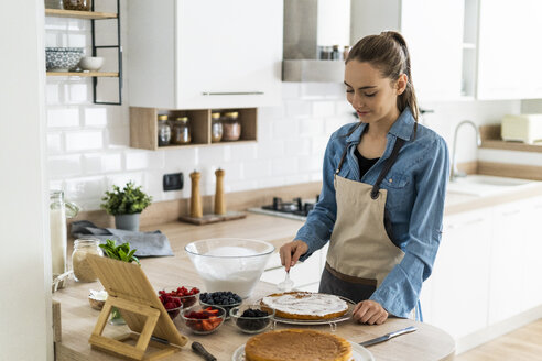 Young woman preparing a cream cake, using tablet - GIOF06190