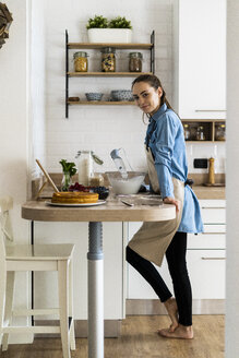 Young woman preparing a cream cake, using tablet - GIOF06193