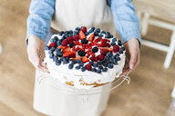 Young woman shwoing a cream cake with fresh fruits - GIOF06208
