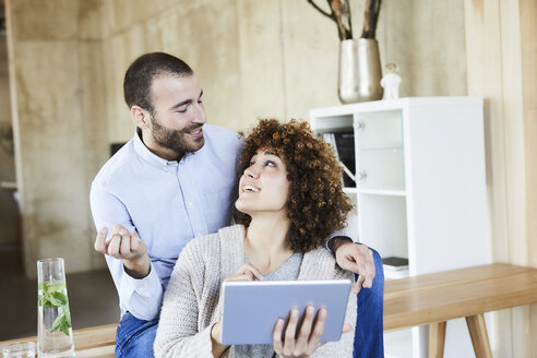 Happy man and woman with tablet talking in modern office - FMKF05555