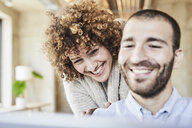 Happy man and woman sharing tablet in modern office - FMKF05558