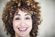 Portrait of sweating laughing woman with curly hair - FMKF05576