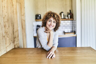 Portrait of smiling woman leaning on wooden table - FMKF05579