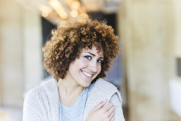 Portrait of smiling woman with curly hair - FMKF05591