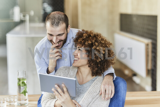 Happy man and woman sharing tablet in modern office - FMKF05594 - Jo Kirchherr/Westend61