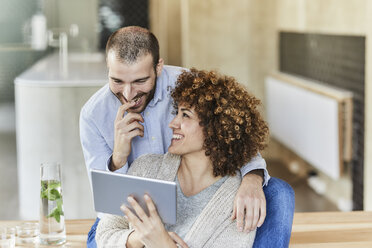 Happy man and woman sharing tablet in modern office - FMKF05594
