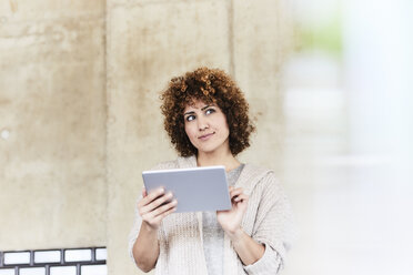 Smiling woman using tablet at concrete wall - FMKF05600