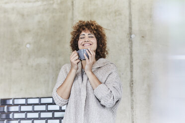 Smiling woman enjoying a coffee at concrete wall - FMKF05603