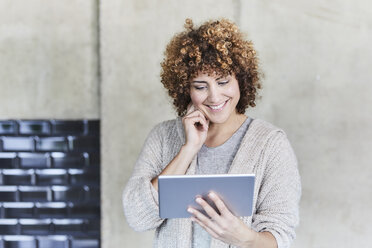 Smiling woman using tablet at concrete wall - FMKF05606