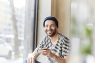 Portrait of smiling young man holding coffee cup at the window - FMKF05609