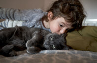 Toddler girl kissing grey cat lying on bed - GEMF02919