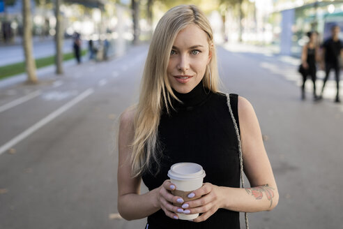 Portrait of smiling blond woman with coffee to go - GIOF06210