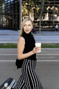 Portrait of smiling blond woman with coffee to go and wheeled luggage - GIOF06213