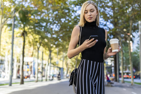 Portrait of blond woman with coffee to go looking at cell phone - GIOF06219