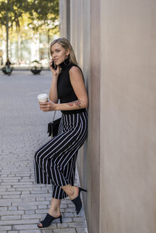 Portrait of smiling blond woman with coffee to go on the phone leaning against wall - GIOF06222