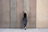 Young blond woman with cell phone leaning against wall drinking coffee to go - GIOF06225