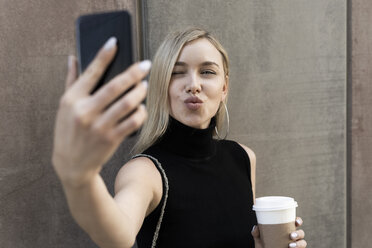 Portrait of blond woman with coffee to go taking selfie with smartphone - GIOF06228