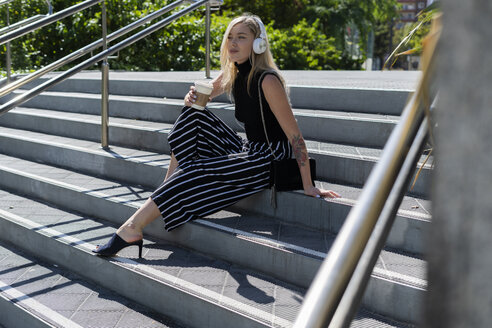 Blond young woman with coffee to go sitting on stairs listening music with headphones - GIOF06231