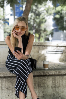 Blond young woman sitting on a wall using cell phone - GIOF06237