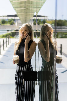Blond young woman with coffee to go on the phone - GIOF06240