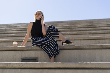 Blond young woman on the phone sitting on stairs outdoors - GIOF06243